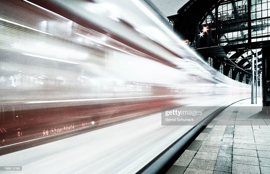 Blurred train at night leaving station : Stock-Foto