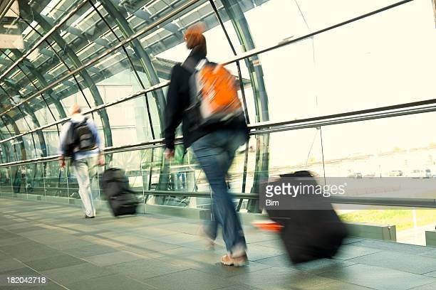 Blurred Travellers Pulling Suitcase Along Hallway in Airport