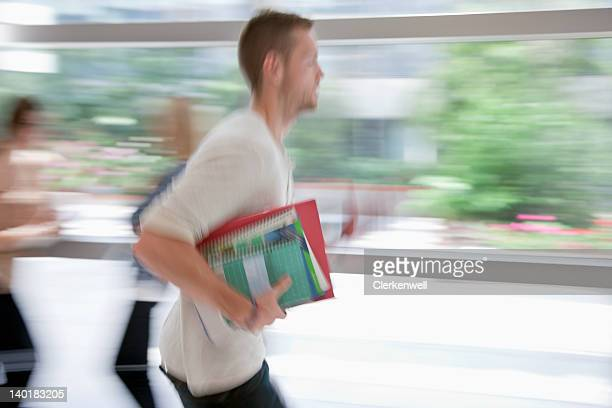 Blurred university student running in corridor with textbooks