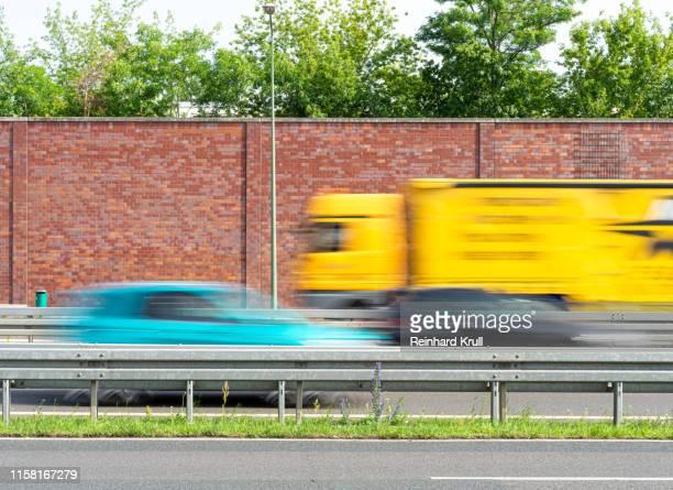 blurred vehicles of road on sunny day - leitplanke stock-fotos und bilder