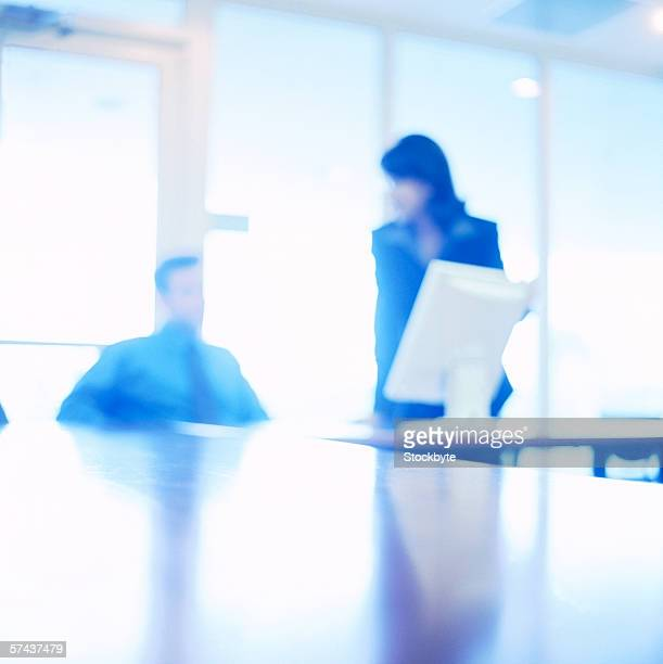 blurred view of a man and woman sitting in an office talking