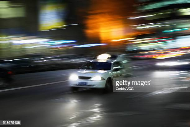 Blurred view of a white taxi cab driving through urban setting at night