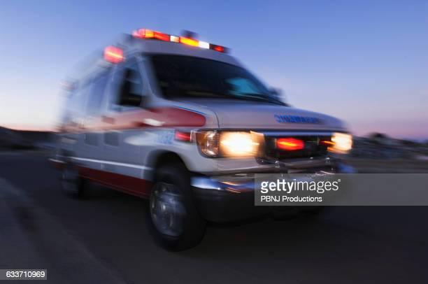 blurred view of ambulance driving at dusk - rettung stock-fotos und bilder