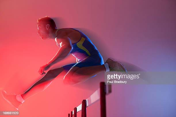 blurred view of athlete jumping hurdles - hurdling stock photos and pictures