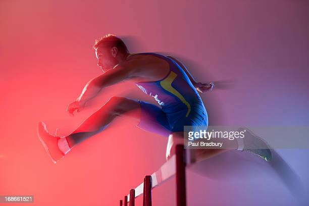 Blurred view of athlete jumping hurdles