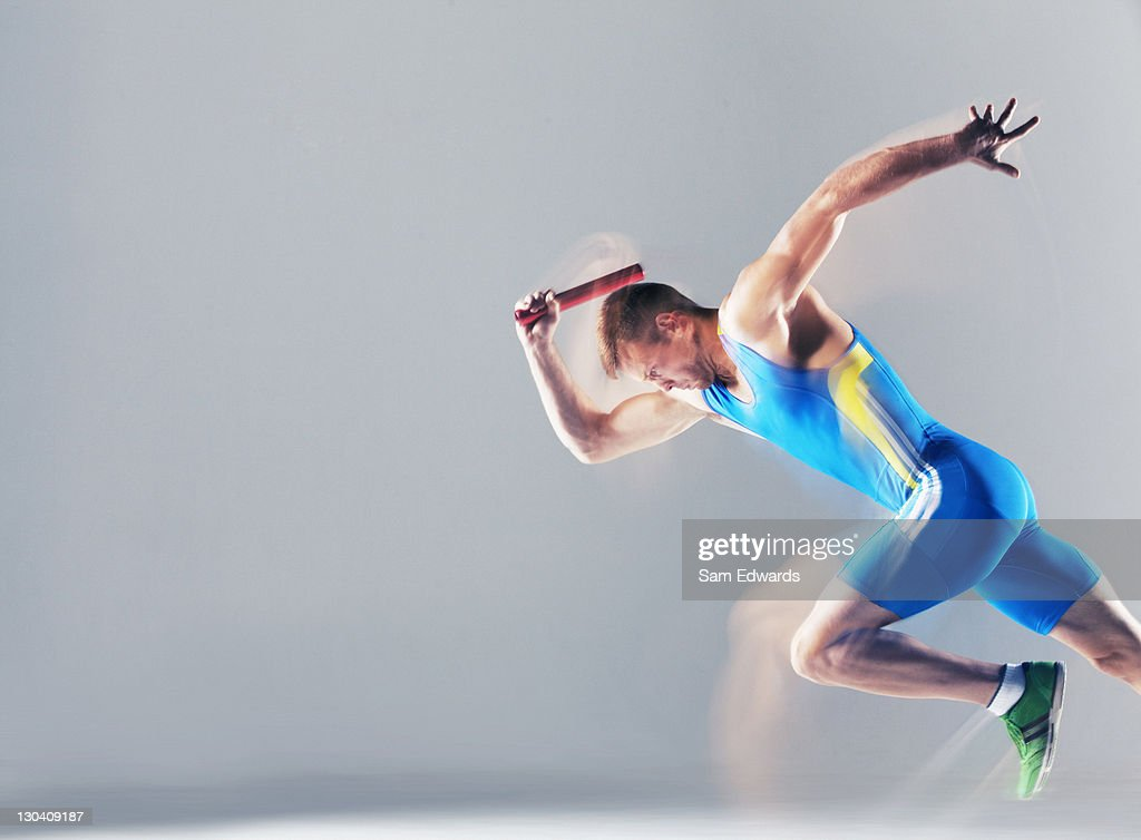 Blurred view of athlete running with baton : Stock Photo