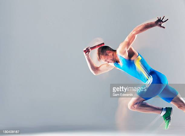 blurred view of athlete running with baton - relay baton stock photos and pictures