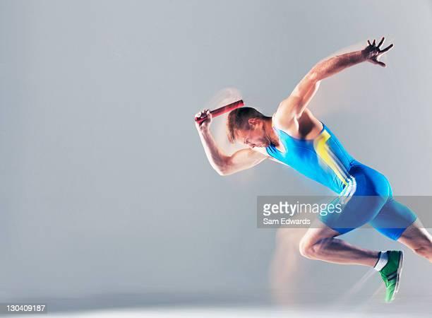 Verschwommene Blick auf Athlet läuft mit baton