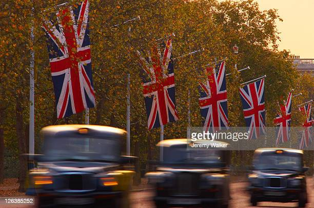 a blurred view of black london taxi cabs driving along the mall at dusk. - ロンドン ザ・マル ストックフォトと画像