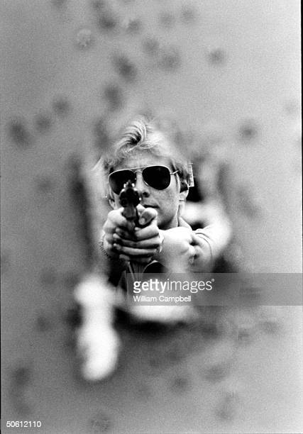 Blurred view of bulletriddled target w a large hole in the middle which frames the focused image of author Patricia Cornwell w a twohanded grip on...