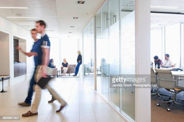 Blurred view of businessmen walking in busy office