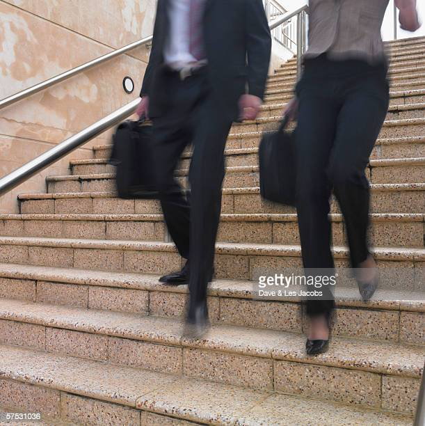 Blurred view of businesspeople's legs descending stairs