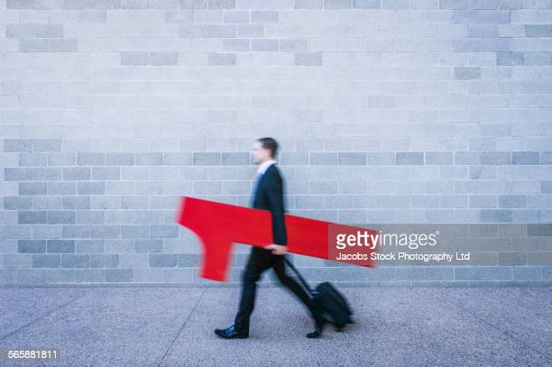 Blurred view of Caucasian businessman carrying number one near brick wall