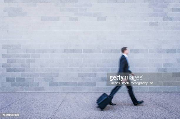 Blurred view of Caucasian businessman rolling luggage near brick wall