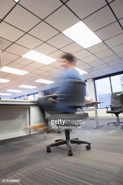 blurred view of caucasian businessman spinning in office chair - spinning stock pictures, royalty-free photos & images