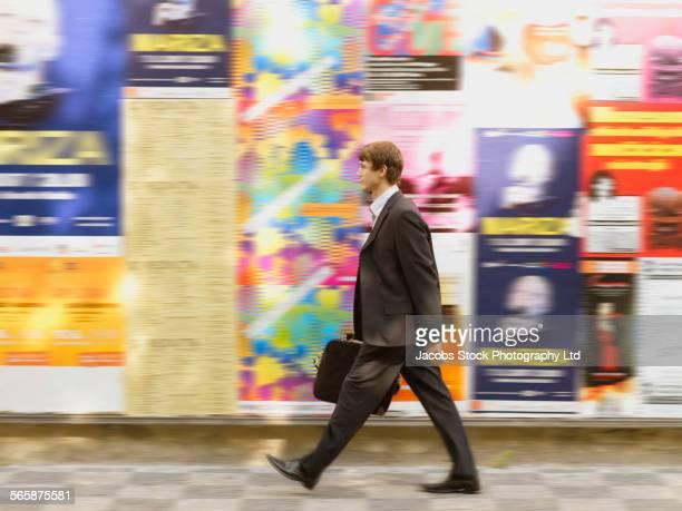 Blurred view of Caucasian businessman walking on city sidewalk