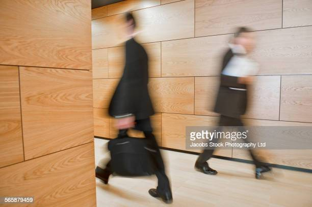 Blurred view of Caucasian businessmen walking in office hallway