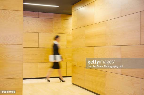 Blurred view of Caucasian businesswoman walking in office hallway