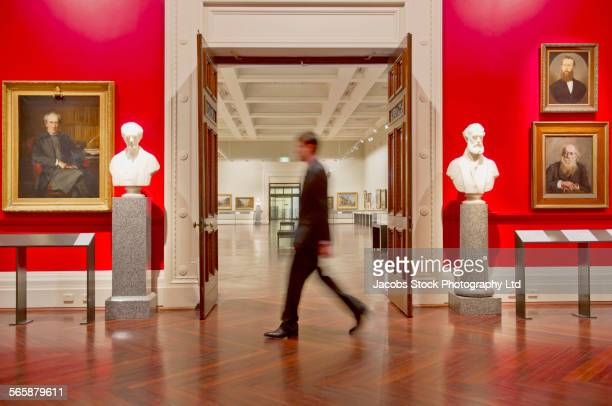 blurred view of caucasian security guard walking in art museum - museum stock pictures, royalty-free photos & images