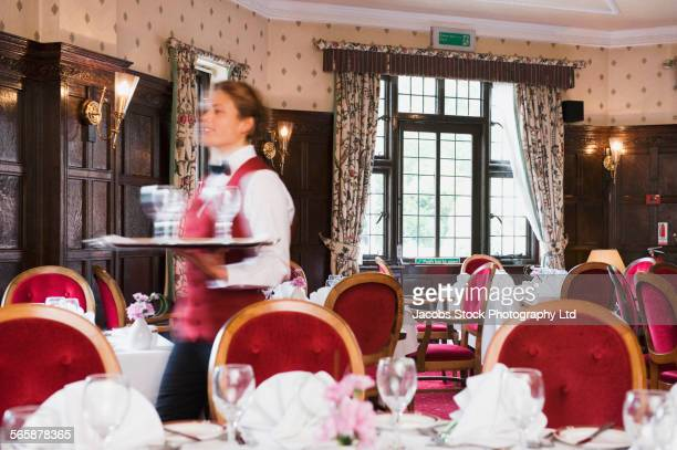 Blurred view of Caucasian waitress walking in empty restaurant