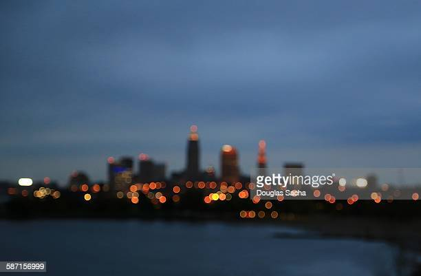 blurred view of city skyline lit up at night - cleveland stock pictures, royalty-free photos & images