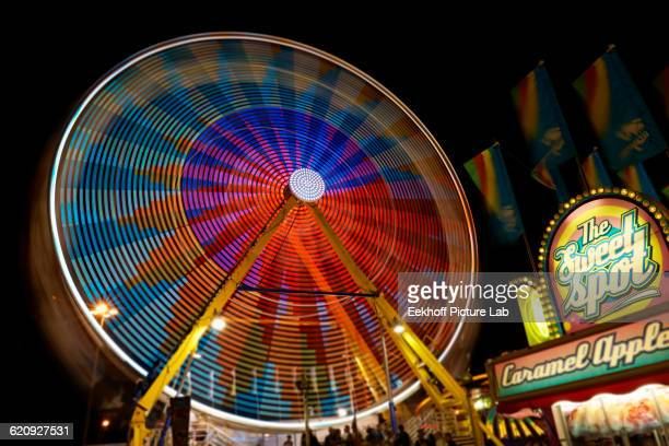 blurred view of ferris wheel at amusement park - canadian national exhibition stock photos and pictures