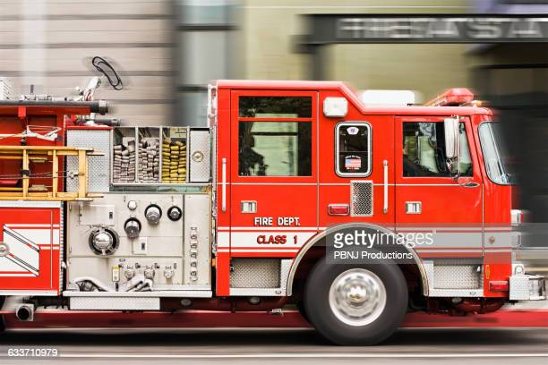 blurred view of fire truck driving in city - carro de bombeiro - fotografias e filmes do acervo