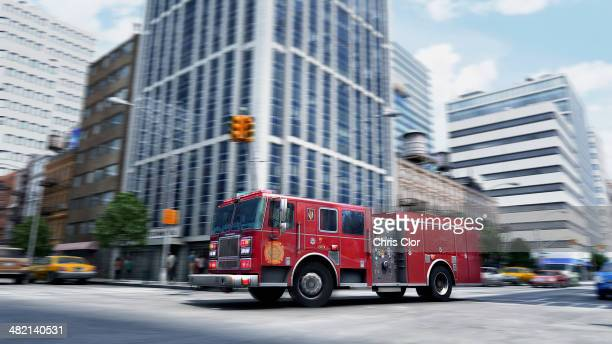 Blurred view of fire truck driving through intersection, New York, New York, United States