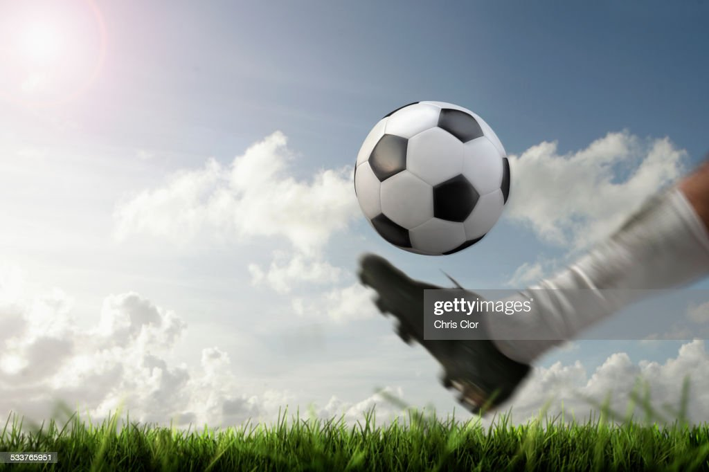 Blurred view of foot kicking soccer ball : Stock Photo