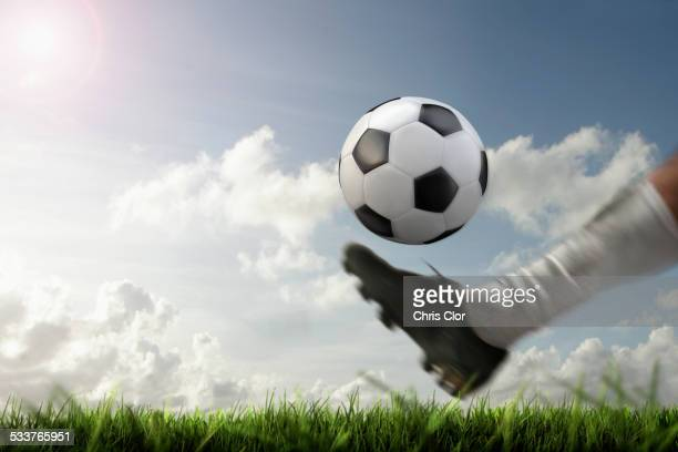 blurred view of foot kicking soccer ball - kicking stock pictures, royalty-free photos & images