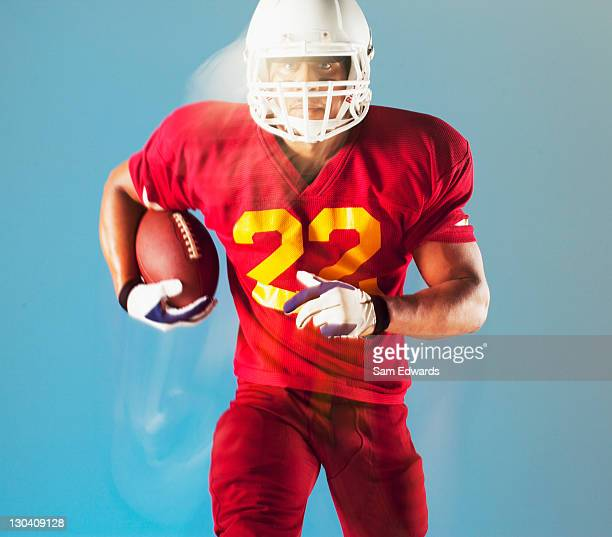 blurred view of football player holding ball - safety american football player stock pictures, royalty-free photos & images