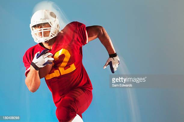 blurred view of football player running with ball - safety american football player stock pictures, royalty-free photos & images