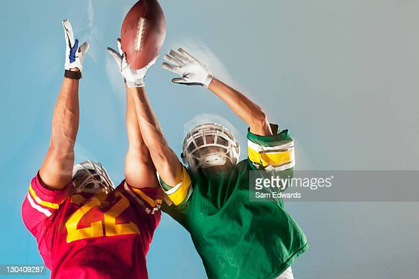 blurred view of football players reaching for ball - safety american football player stock pictures, royalty-free photos & images