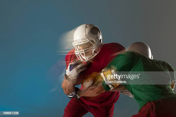 blurred view of football players with ball - tackling stock pictures, royalty-free photos & images