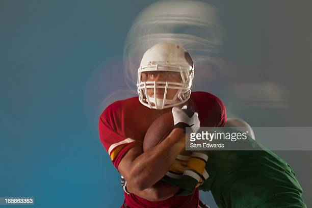 borrosa vista de los jugadores de fútbol con pelota - rush fútbol americano fotografías e imágenes de stock