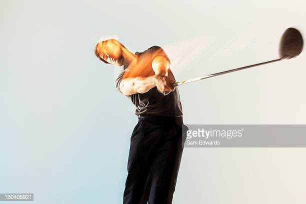 Blurred view of golf player swinging club