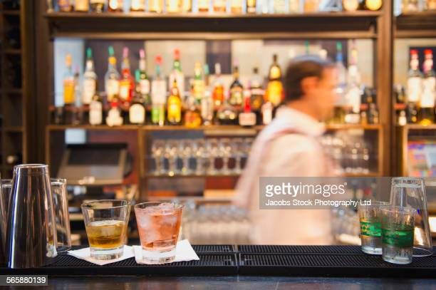 Blurred view of Hispanic bartender working behind bar