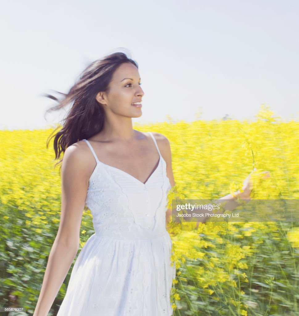 Blurred view of Indian woman walking in field of flowers : Stock Photo