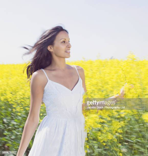 Blurred view of Indian woman walking in field of flowers