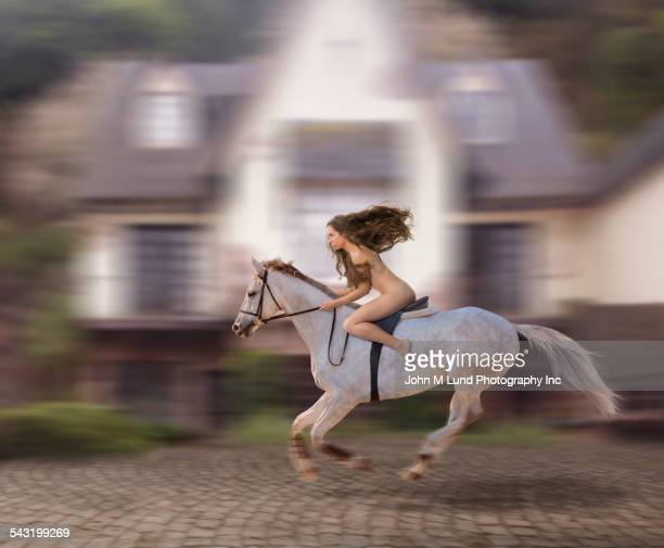 Blurred view of nude Caucasian woman riding horse