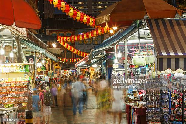 Blurred view of people shopping in outdoor market at night