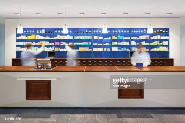 blurred view of pharmacists behind counter in modern pharmacy - pharmacy stock pictures, royalty-free photos & images