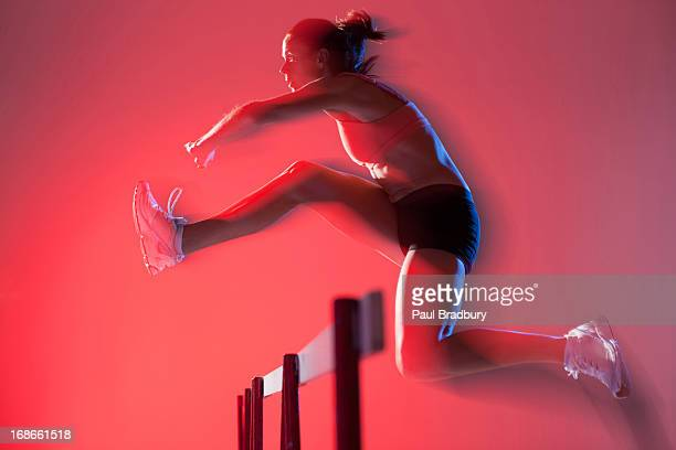 blurred view of runner jumping hurdles - hurdling track event stock pictures, royalty-free photos & images