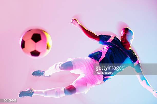 blurred view of soccer player kicking ball - studio shot stockfoto's en -beelden