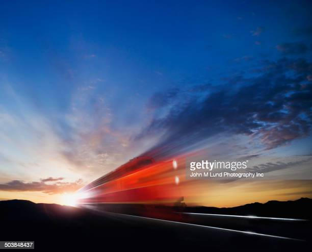Blurred view of train under sunset sky