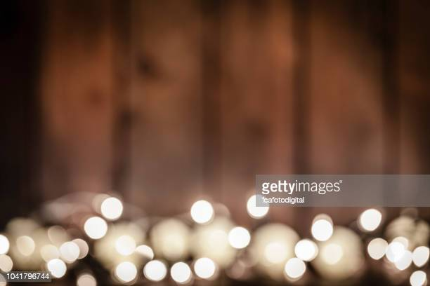 blurred wooden table with christmas lights background - country christmas stock pictures, royalty-free photos & images