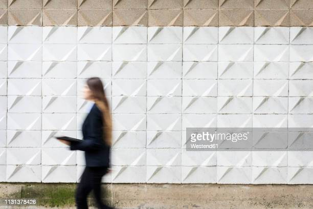 blurred young businesswoman holding tablet passing concrete wall - businesswear stock pictures, royalty-free photos & images