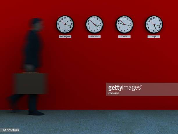 A blurry businessman walking toward four clocks