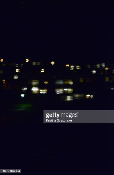 blurry city lights at night, seen through blinds - kristina strasunske stock photos and pictures