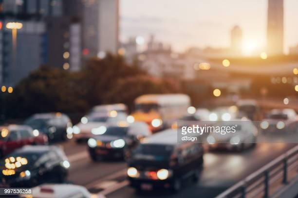 blurry image of rush hour traffic on busy highway at sunset - traffico foto e immagini stock